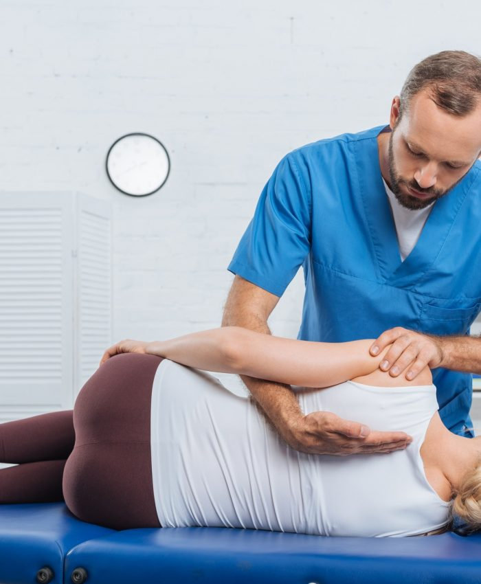 Osteopath massaging back of patient that lying on massage table in clinic